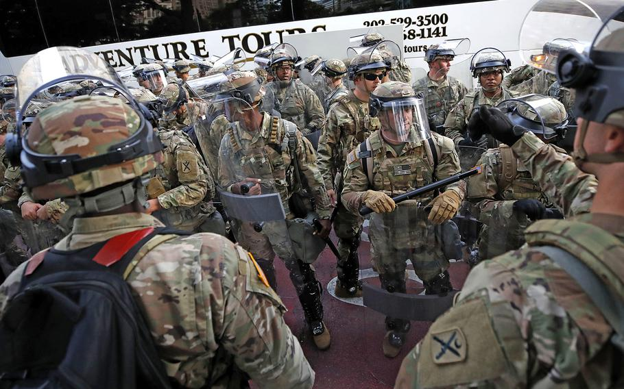 Soldiers with the South Carolina National Guard arrive on buses as demonstrators continue to protest the death of George Floyd, Wednesday, June 3, 2020, near the White House in Washington.