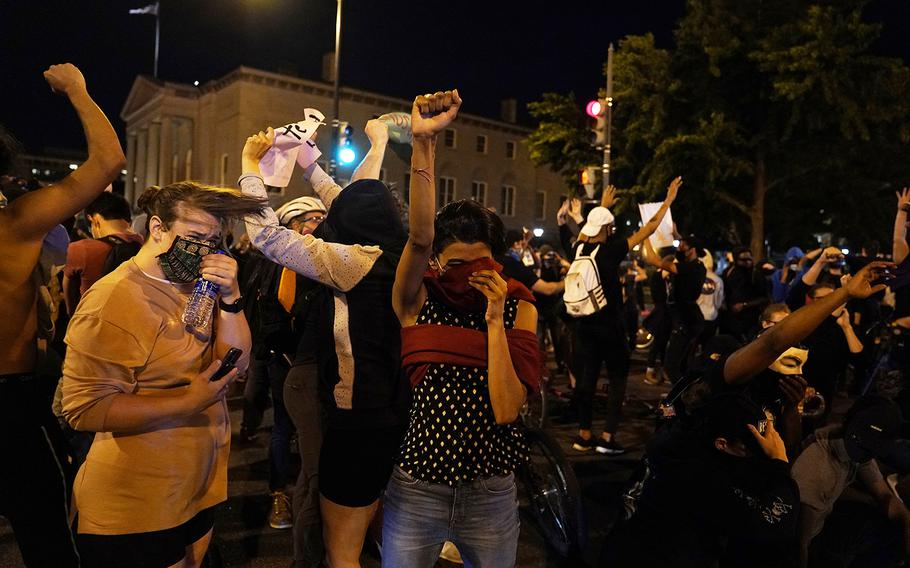 Demonstrators react as a helicopter circles low as people gather to protest the death of George Floyd, Monday, June 1, 2020, near the White House in Washington. Floyd died after being restrained by Minneapolis police officers.
