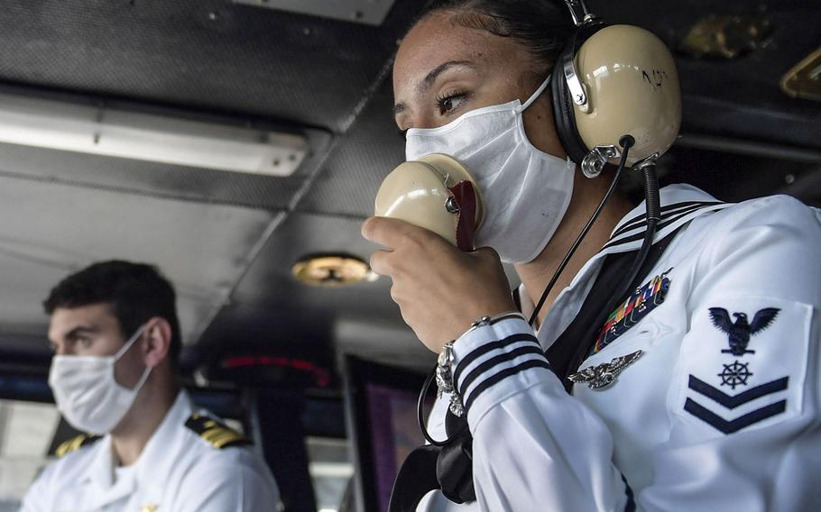 U.S. Navy Quartermaster 2nd Class Reyna Montueuses uses a sound powered phone in the navigation bridge of the aircraft carrier USS Theodore Roosevelt while departing Apra Harbor, Guam, June 4, 2020.