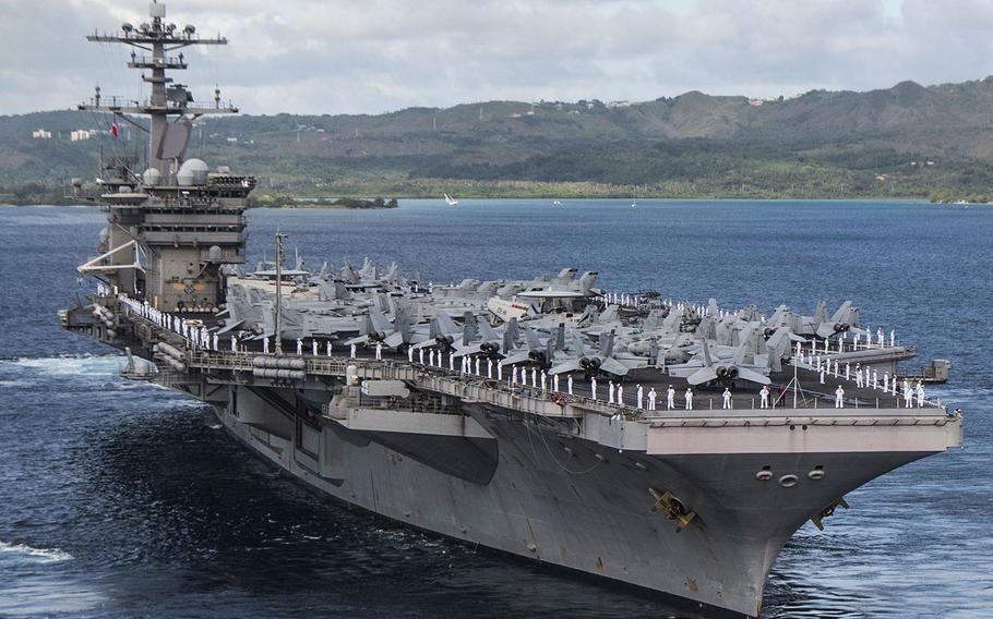 Sailors man the rails as the aircraft carrier USS Theodore Roosevelt departs Apra Harbor, Guam, June 4, 2020.