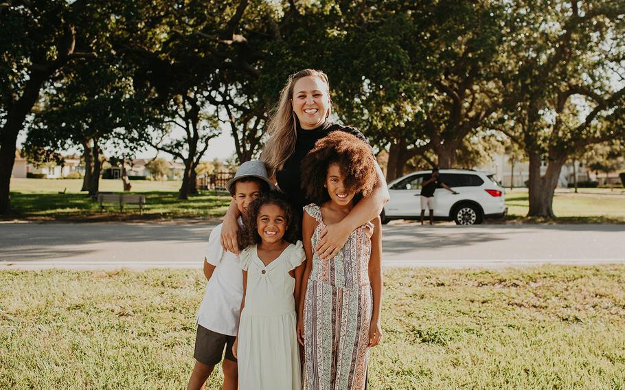Kristin McKenzie and her kids (left to right) Grey, Lawton and Blake posed for photos as a white SUV pulled up in the background.