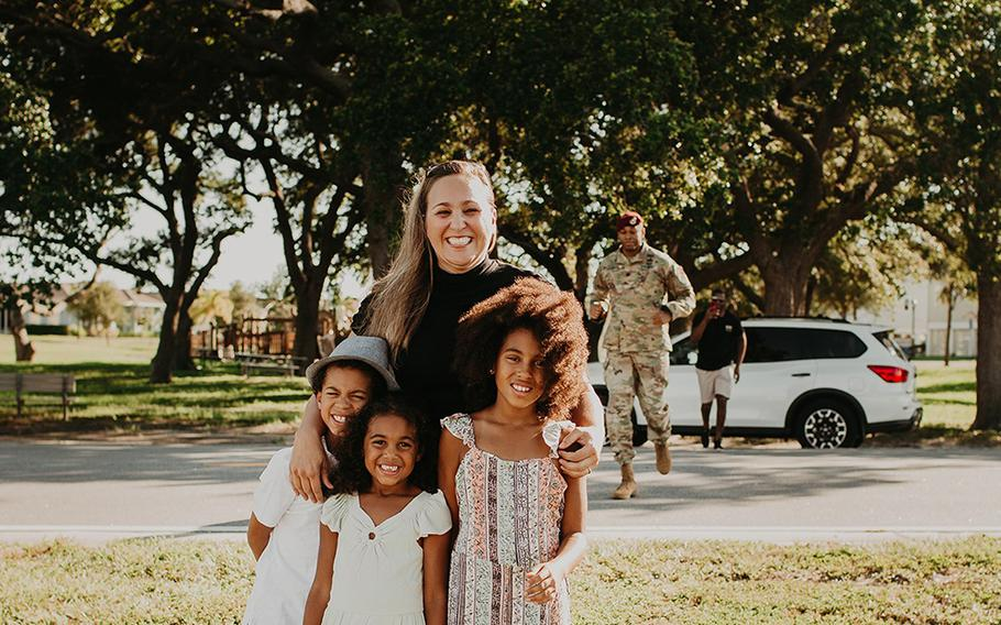Lt. Col. Simon McKenzie gets ready to surprise his family during a photo shoot as wife Kristin McKenzie poses for photos with their kids (left to right) Grey, Lawton and Blake.