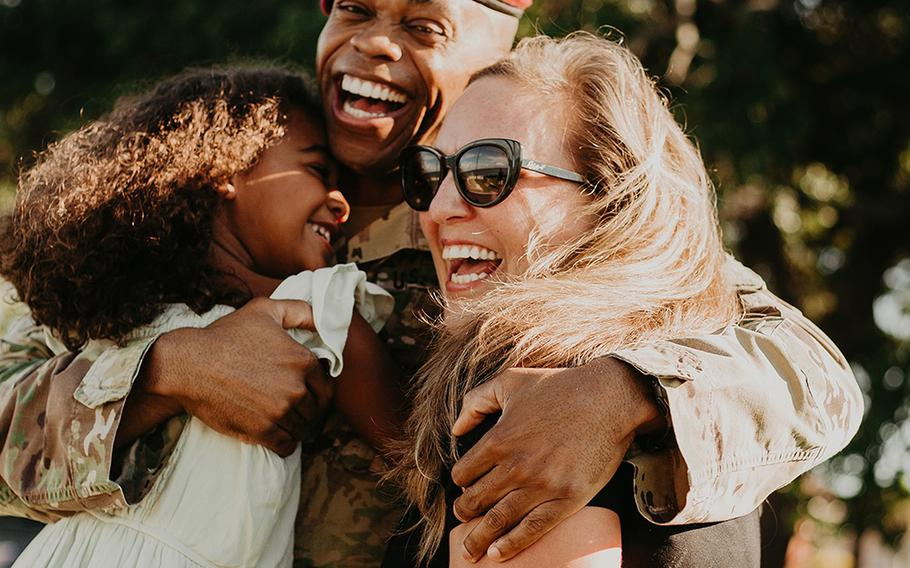 Lt. Col. Simon McKenzie smiles as he hugs daughter Lawton and wife Kristin after his 2020 deployment.