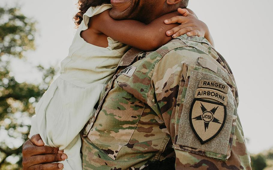 Lt. Col. Simon McKenzie is all smiles as he reunites with his family after his deployment.