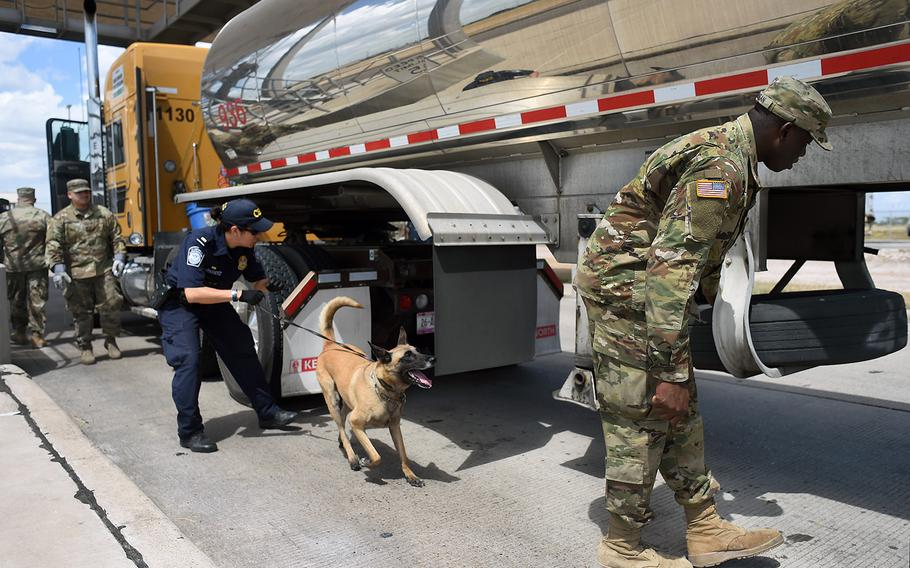 Spc. Afeez Amusan, right, a truck driver with the Texas Army Guard's Company A, 536th Brigade Support Battalion, inspects a tractor-trailer truck alongside a U.S. Customs and Border Protection agent at the Pharr, Texas, port of entry facility on Aug. 21, 2018.