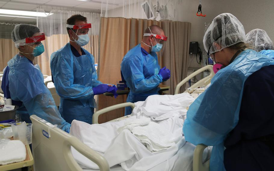 In a July 10, 2020 photo, U.S Army critical care nurses 1st Lt. Charles Gilcrist, 1st Lt. Lauryn Hudgins and 1st Lt. Colton Whitehouse from Urban Augmentation Medical Task Force - 627 work to provide medical care to a COVID-19 patient alongside Baptist Hospital medical staff, in San Antonio, Texas.