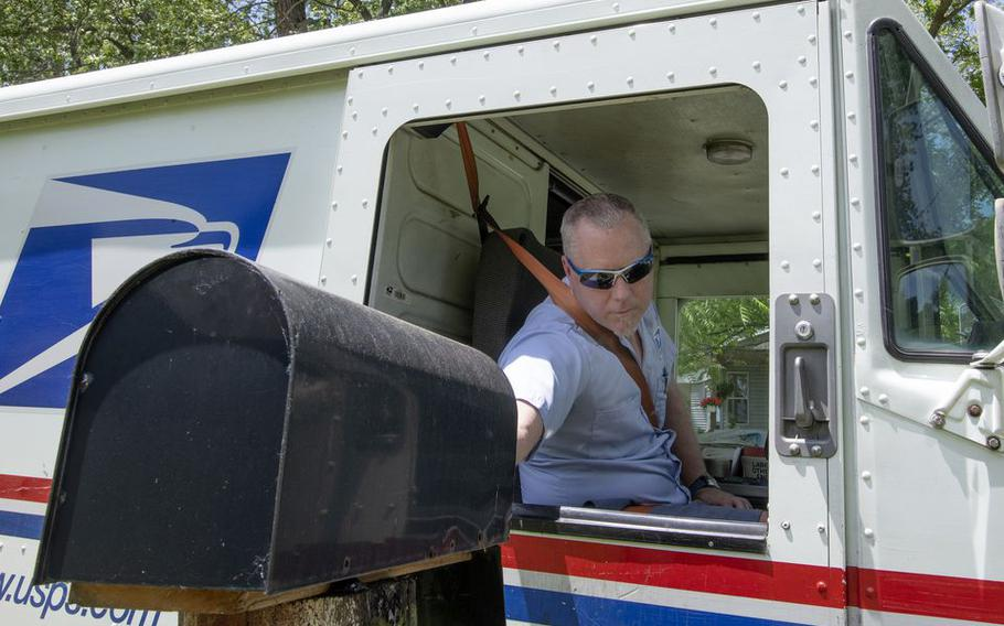 United States Postal Service carrier Joshua Davis delivers mail on his Jackson, Mich.-area route on Tuesday, June 9, 2020.