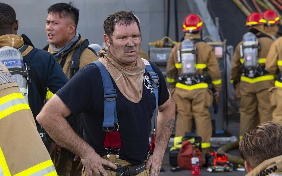 Firefighter John Farrell, from Federal Fire Station 13 at Naval Amphibious Base Coronado, emerges from USS Bonhomme Richard.