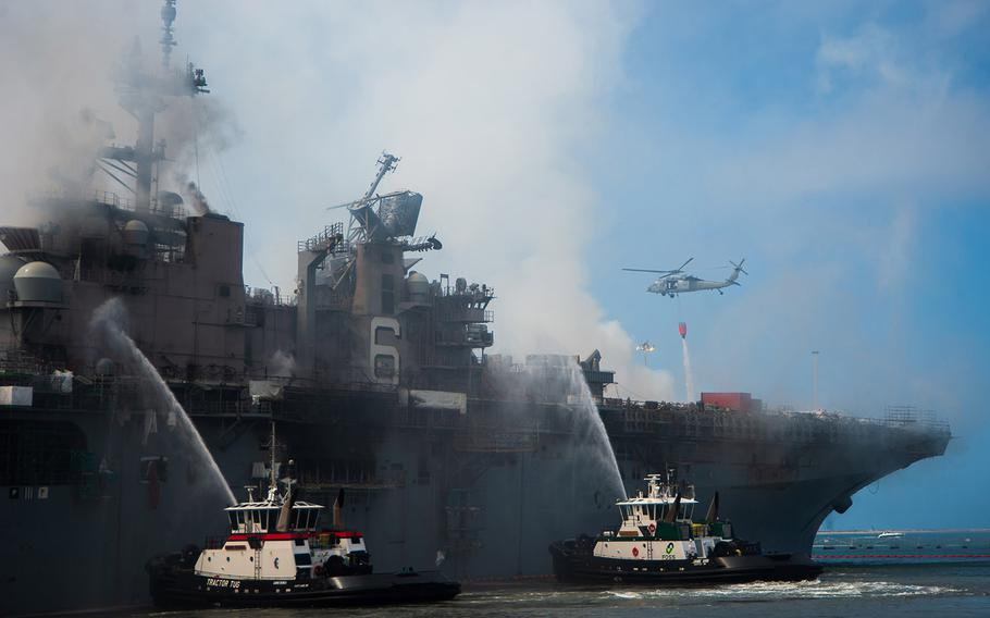An MH-60S Seahawk helicopter, provides aerial firefighting support alongside sailors and civilian fire crews on the ground to fight the fire aboard amphibious assault ship USS Bonhomme Richard on July 13, 2020. On the morning of July 12, a fire was called away aboard the ship while it was moored pier side at Naval Base San Diego.