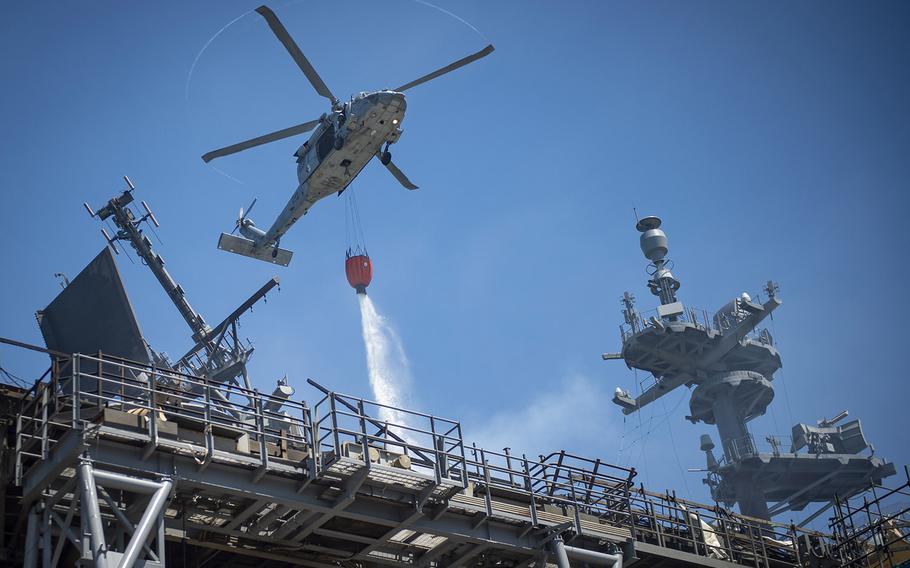 An MH-60S Sea Hawk helicopter combats a fire aboard the USS Bonhomme Richard on July 14, 2020. On the morning of July 12, a fire was called away aboard the ship while it was moored pier side at Naval Base San Diego. Base and shipboard firefighters responded to the fire.