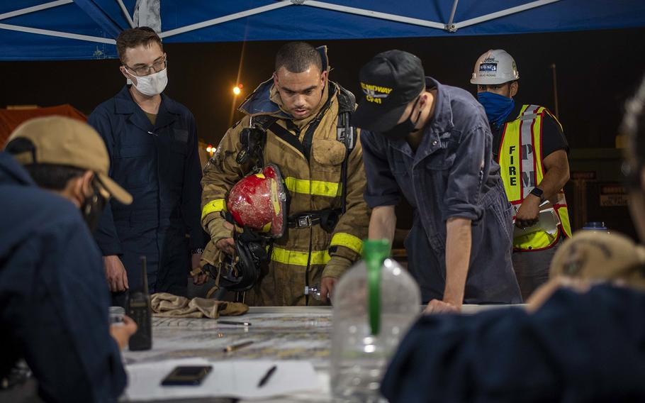 Sailors discuss ongoing firefighting operations aboard the amphibious assault ship USS Bonhomme Richard at Naval Base San Diego on July 14, 2020.