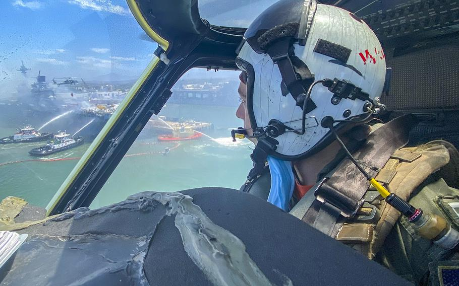 Lt. Matthew Wellens flies an MH-60S Seahawk helicopter to support aerial firefighting operations aboard the USS Bonhomme Richard on July 13, 2020.