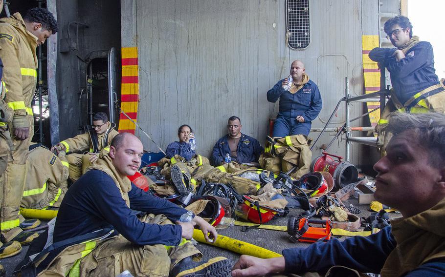 Sailors rest after battling a fire aboard the amphibious assault ship USS Bonhomme Richard on July 14, 2020.