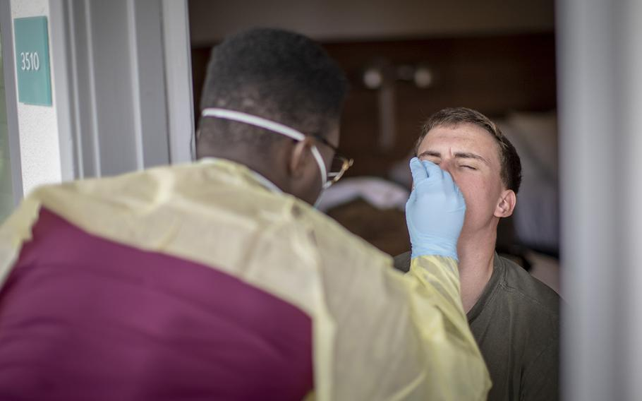 U.S. Navy Hospital Corpsman 3rd Class Brandon Smith, left, performs a COVID-19 swab test on a Marine ain San Diego on June 22, 2020.