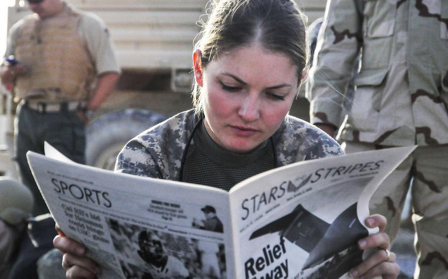 First Lt. Tracy Tyson from Seattle, Wash., assigned to the 5th Brigade 2nd Infantry Division, reads Stars and Stripes at Kandahar Airfield, Afghanistan, while waiting for a flight to Forward Observation Base Wolverine in 2009.