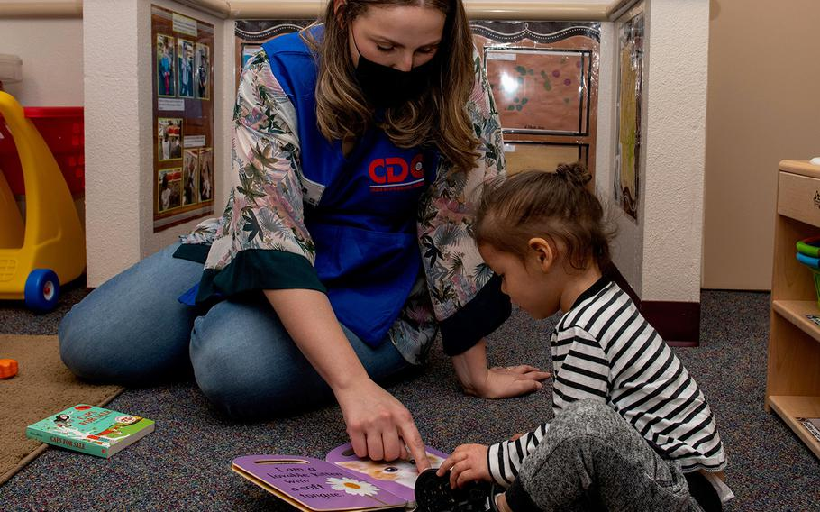 In a May 1, 2020 photo, Emilia Williams, 60th Force Support Squadron child and youth program technician, helps a child read a book at Child Development Center 3 at Travis Air Force Base, Calif.