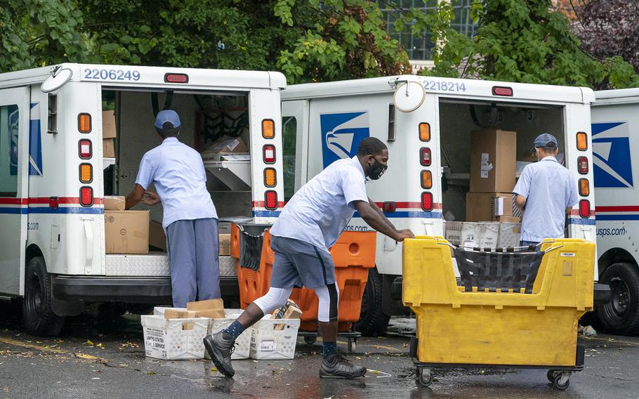 Letter carriers load mail trucks for deliveries at a U.S. Postal Service facility in McLean, Va., on July 31, 2020.