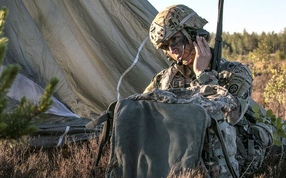 In a  June 9, 2018 photo, Capt. Shaye Haver, commander of Company C., 1st Battalion, 508th Parachute Infantry Regiment, 3rd Brigade Combat Team, 82nd Airborne Division, Fort Bragg, N.C., performs radio checks on Adazi Base, Latvia, after parachuting from a C-17 Globemaster III during Swift Response 18.