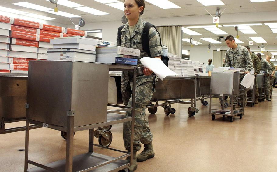 In a 2016 photo, first-year medical students at the F. Edward Hebert School of Medicine at the Uniformed Services University of the Health Sciences receive more than 140 pounds of books each inside the anatomy lab. A Politico report says the university is one of the DOD's targets for a considerable funding reduction.