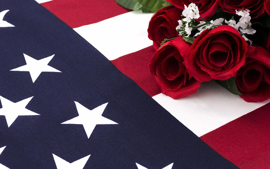 Close shot of roses laying on top and wrapped in American flag