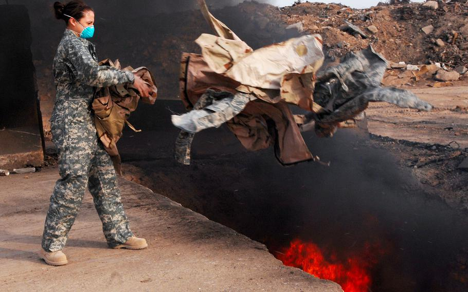 An equipment manager with the 332nd Expeditionary Logistics Readiness Squadron, tosses unserviceable uniform items into a burn pit in Iraq in 2008.