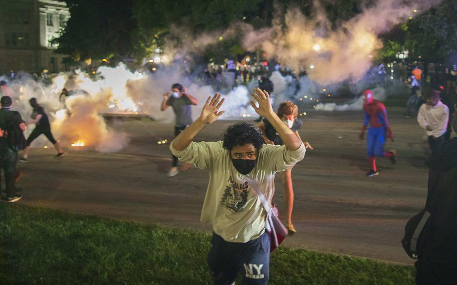 Tear gas lands around protesters after they refused to listen to police demands to disperse near the courthouse in Kenosha, Wisconsin on Tuesday, August 25, 2020.