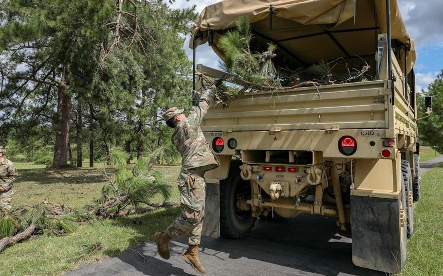 Cpl. Sebastian Tabarez, a preventative medicine specialist with C Co, 710th BSB, 3rd IBCT, 10th Mountain Division, loads debris into the back of a LMTV during hurricane recovery cleanup on Fort Polk.