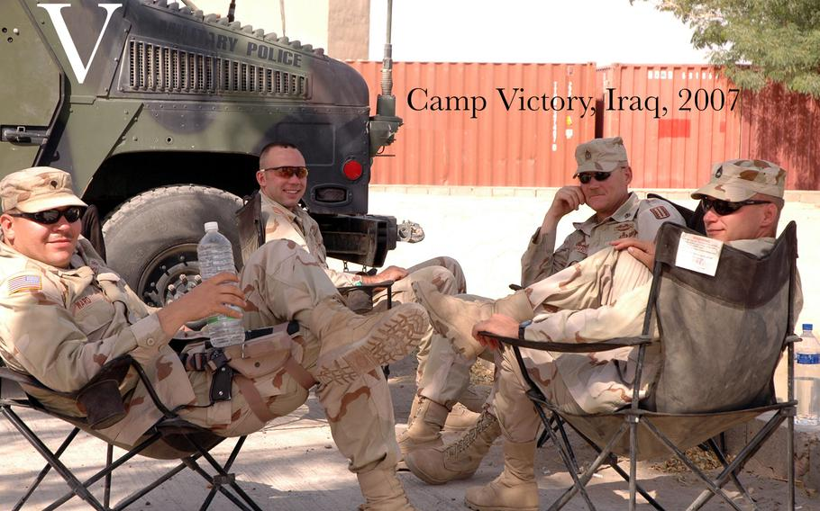 From left to right:  Spc. Levi Ward, Spc. Brian Gordiel, 1st Sgt. William Degenhardt, and Sgt. 1st Class John Sury, take a break under a palm tree Aug. 27, 2005 at Camp Victory, Iraq.  The troops are members of the Illinois Army National Guard's 2nd Battery, 123rd Field Artillery Regiment, stationed at the International Zone, Iraq.