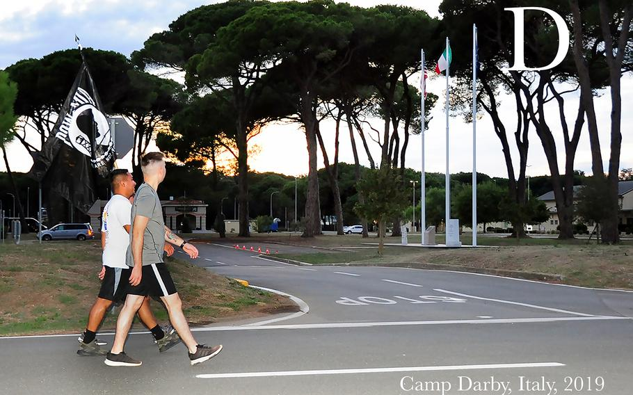 """Two U.S Soldiers during the MIA/POW 24-hour Recognition Run held at Camp Darby, Italy, Sep 19, 2019. The Memorial run was held to remember the sacrifices and service of those who were prisoners of war (POW), as well as those who were missing in action (MIA), and their families. The flag displays a silhouette of a prisoner of war in front of a guard tower and the motto """"You Are Not Forgotten"""" appears below the silhouette. The United States' National POW/MIA Recognition Day is observed across the nation on the third Friday of September each year."""