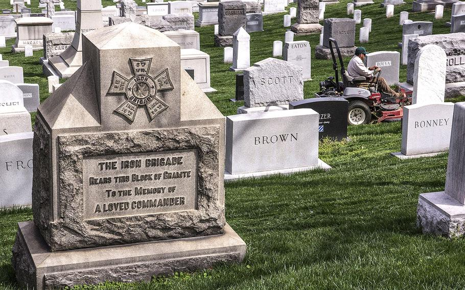 An Arlington National Cemetery worker mows the grass on gravesites in 2017.