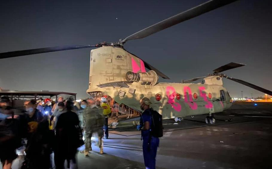 Evacuees from the Creek Fire in Fresno County, Calif., walk off a CH-47 Chinook from the 40th Combat Aviation Brigade of the California National Guard on Saturday evening.
