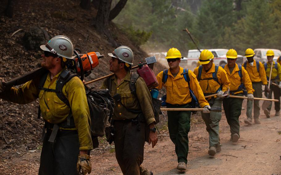 A Billings, Mont.-based crew from the Bureau of Land Management lead soldiers with the 14th Brigade Engineer Battalion on Sept. 6, 2020, as they prepare a road for burnout operations at the August Complex Fire in Mendocino National Forest. Burnout operations involve clearing out easily combustible wildfire fuel such as trees and foliage, helping prevent the fire's spread.