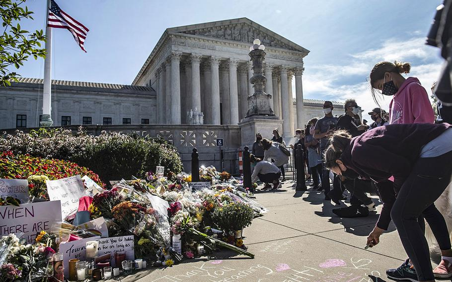 Mourners leave flowers and messages on the sidewalk outside the Supreme Court in Washington, D.C., on Saturday, Sept. 19, 2020, as the American flag is flown at half-staff in honor of the passing of Supreme Court Justice Ruth Bader Ginsburg.