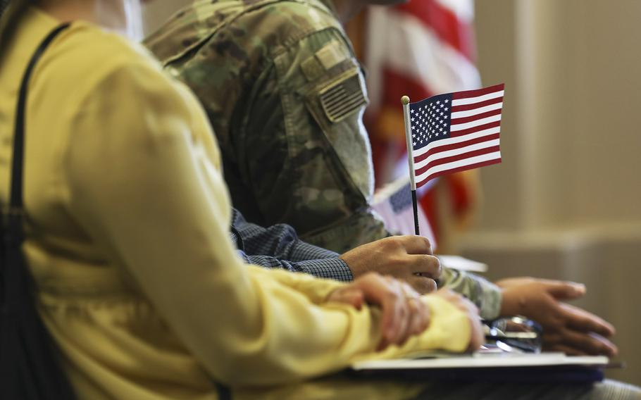 A U.S. flag is held during a naturalization ceremony at the Army Community Services on Fort Carson, Colo., Sep. 20, 2019.
