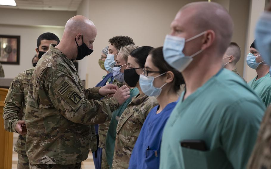 Army Lt. Col. Jason Hughes, commander of Urban Augmentation Medical Task Force-627, pins an award to a soldier under his command at Baptist Medical Center in San Antonio, Texas, Sept. 3. The task force is made up of soldiers with various medical specialties from the 627th Hospital Center at Fort Carson, Colo., and deployed to support San Antonio hospitals during the coronavirus pandemic.