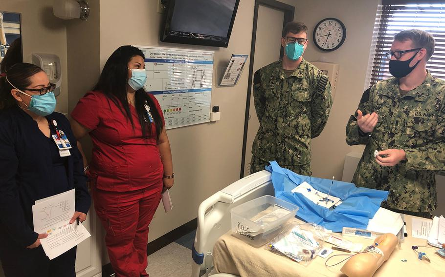 Navy Rural Rapid Response Team 1 members Lt. j.g. Ryan Peare (right) and Ensign Dalton Parker (second from right) instruct the Val Verde Regional Medical Center clinical staff in arterial and central line management procedures at Val Verde Regional Medical Center, Del Rio, Texas, Sept. 3.