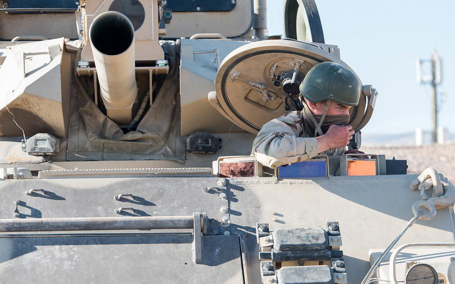 A soldier with the Army's 11th Armored Cavalry Regiment enters an armored vehicle at the National Training Center at Fort Irwin, Calif., on Sept. 20. The 11th ACR serves as an opposing force at the massive installation in the Mojave Desert, testing the skills of rotational units training at NTC.