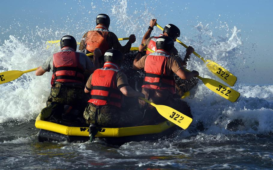 Senior officers and enlisted men paddle into the surf at Naval Amphibious Base Coronado during Surf Passage, a part of the first phase of SEAL training, Nov. 8, 2016.