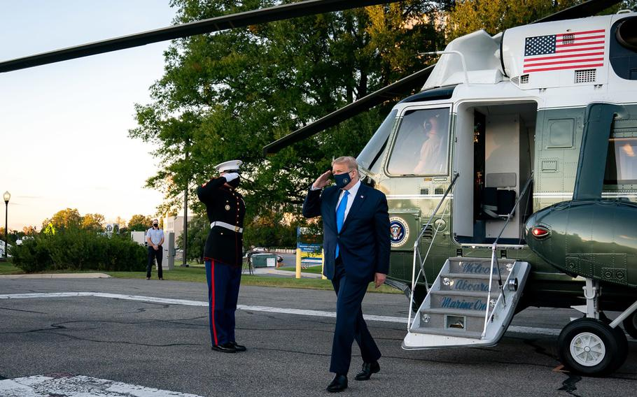 President Donald Trump salutes as he disembarks Marine One upon arrival to Walter Reed National Military Medical Center on Friday, Oct. 2, 2020, in Bethesda, Md