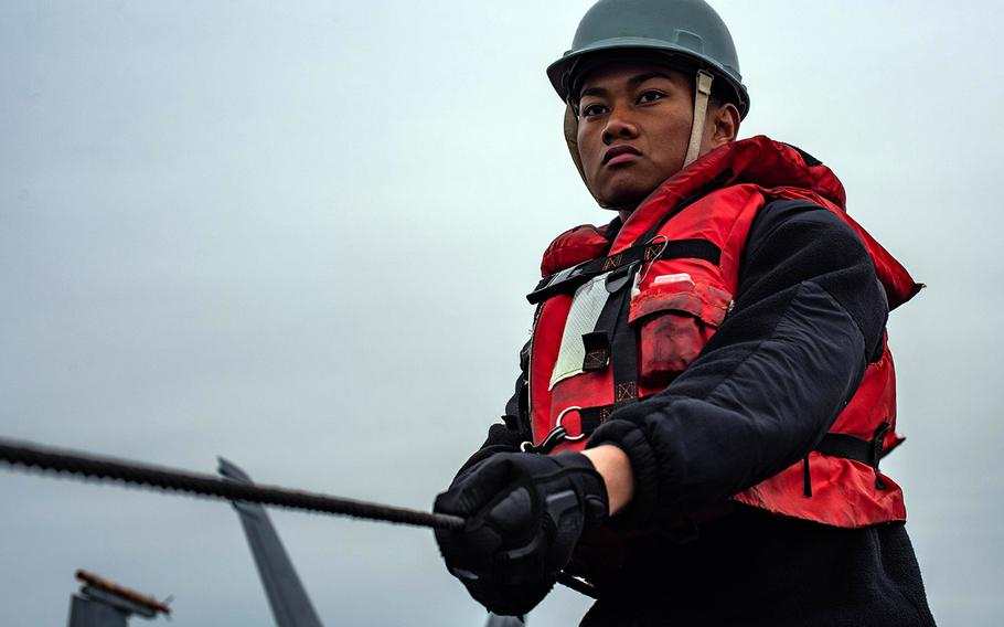 Seaman Isaiah Peralta holds the phone and distance line on the flight deck of the aircraft carrier USS Theodore Roosevelt during a replenishment-at-sea Dec. 3, 2019.