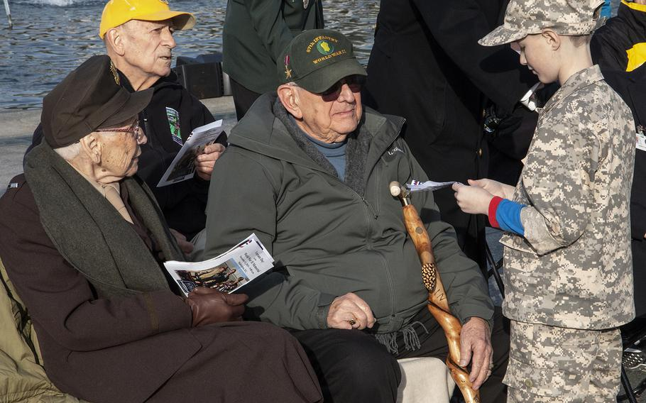 A young admirer talks to veterans at the National World War II Memorial in Washington, D.C., on Veterans Day 2019.