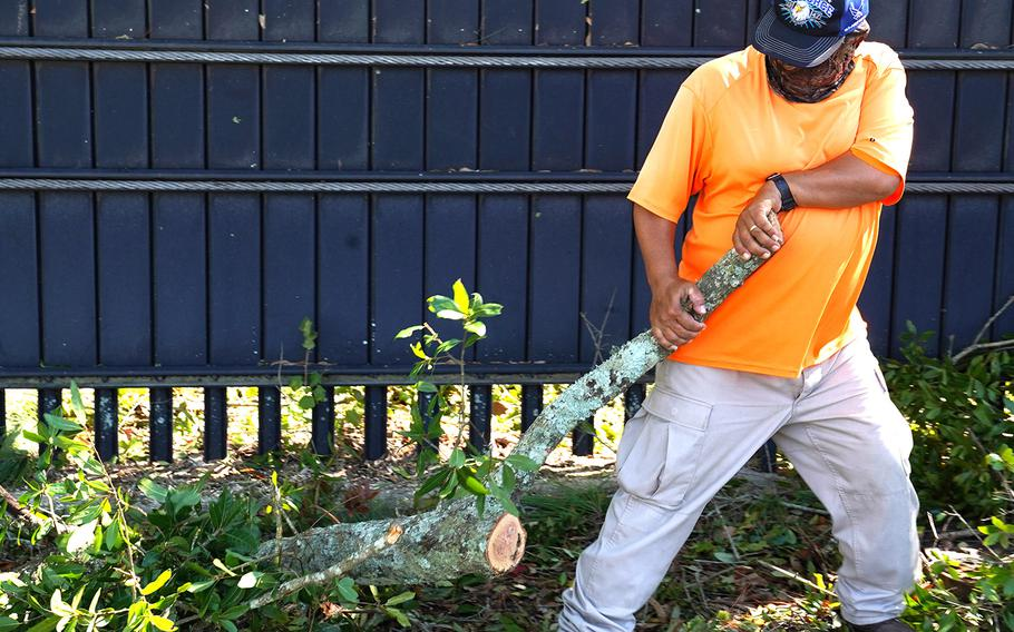 Adan Cardoza, a Vectrus ground landscaping maintainer, cleans up debris at Keesler Air Force Base, Miss., Oct. 29, 2020, in the wake of Hurricane Zeta.