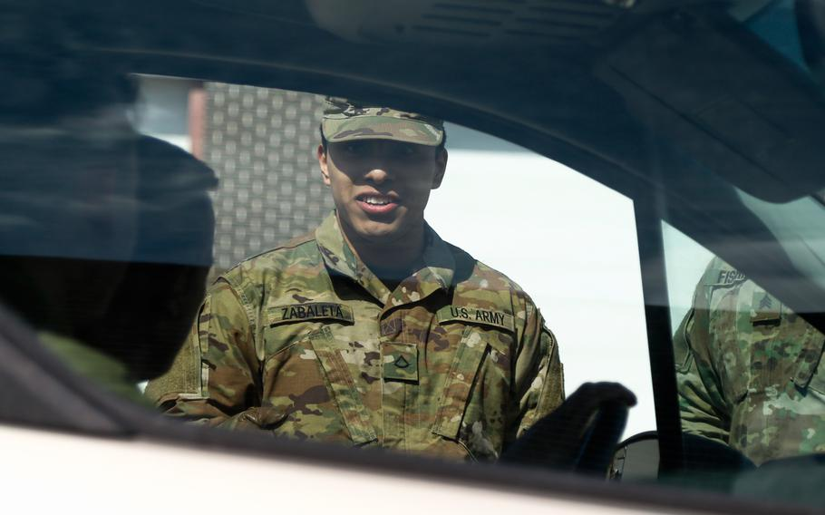 A Wisconsin National Guardsman directs a vehicle on March 21, 2020.