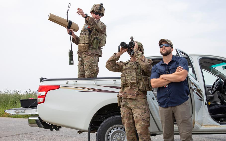 U.S. Army Sgt. Gage Stancell, right, looks through binoculars as Sgt. Gentry Squier describes where he saw a drone during an unmanned aerial system training exercise at Irbil Air Base in the Kurdistan Region of Iraq on April 24, 2020.