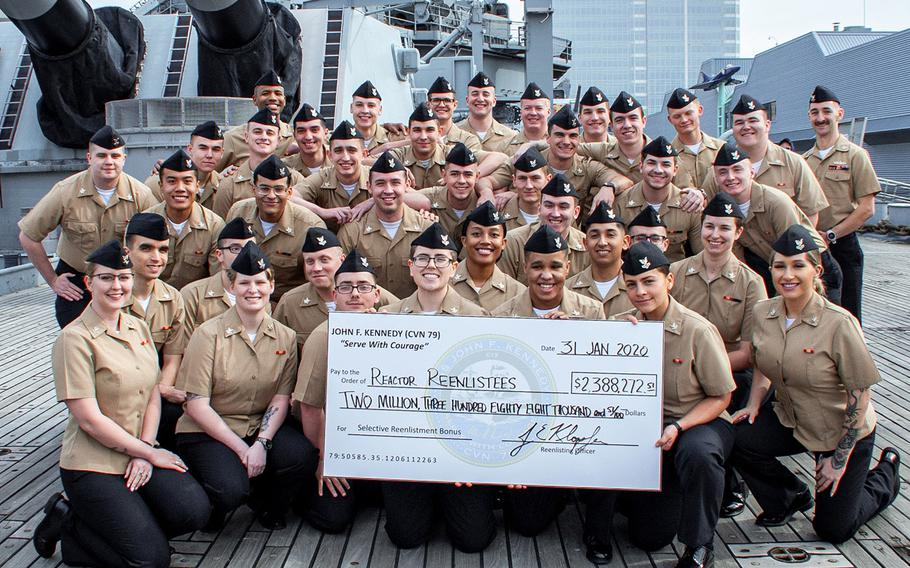 In a January, 2020 photo, Pre-Commissioning Unit John F. Kennedy Reactor Department sailors stand with their reenlistment check onboard the Battleship USS Wisconsin after their group reenlistment that earned them Selective Reenlistment Bonuses.