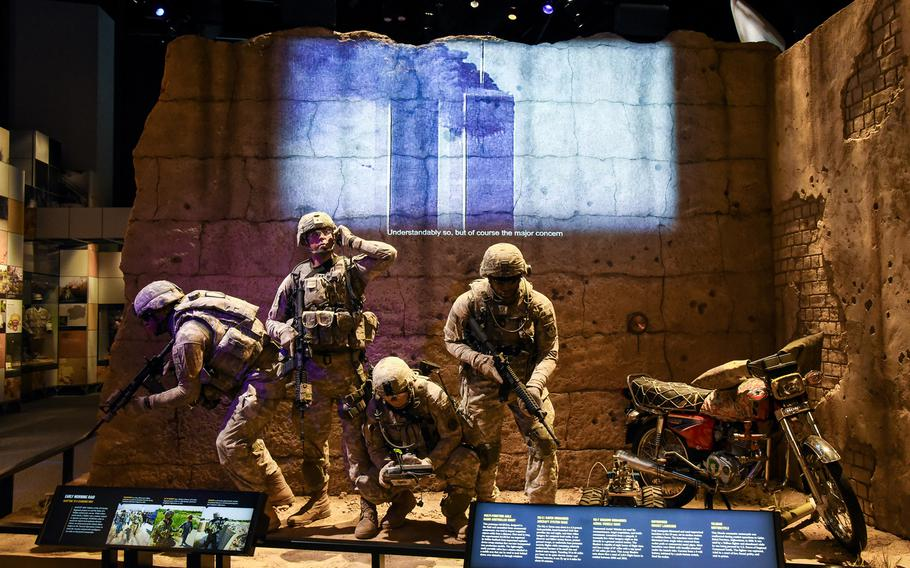 Cast figures depict American soldiers operating in Afghanistan as a video in the background shows news footage of the Sept. 11, 2001 terrorist attacks on the World Trade Center in New York, inside the new National Museum of the United States Army's Changing World Gallery. The gallery shares the Army's story from 1990 until today and feature artifacts from Afghanistan and Iraq.