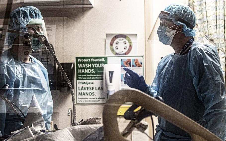 """U.S. Air Force Lt. Col. Charles """"Brock"""" Miller, M.D., right, assigned to the 59th Medical Wing at Lackland Air Force Base, Texas, talks with a nurse about patient care at the University Medical Center in El Paso, Texas, Nov. 11, 2020."""