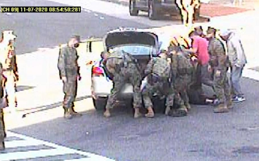 A video screenshot shows Marines in Washington, D.C., responding to an accident in which a woman was pinned underneath a car on Nov. 7, 2020. The Marines lifted the car using two jacks, saving vital time for fire and rescue officials who arrived on the scene shortly afterward.