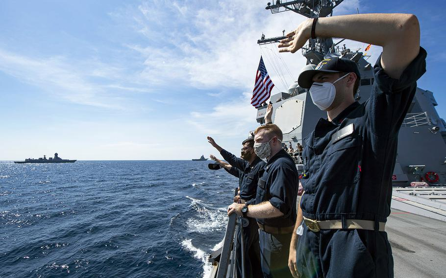 In a Nov. 20, 2020 photo, sailors on board the guided-missile destroyer USS Sterett wave to the crew of an Indian Navy vessel during Malabar 2020.