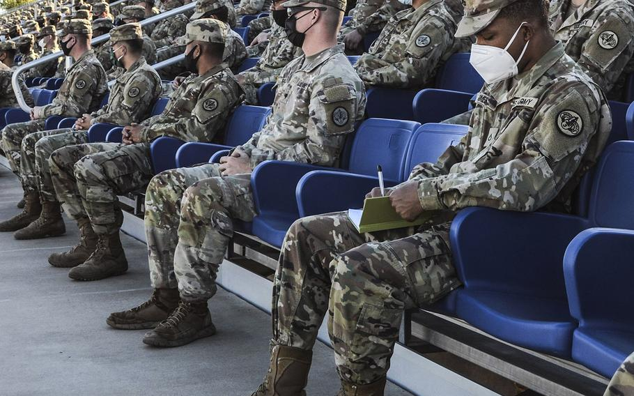A soldier takes notes  as Lt. Gen. Pat White and Command Sgt. Maj. Cliff Burgoyne Jr., commander and senior noncommissioned officer of III Corps and Fort Hood, addresses about 2,000 soldiers at Fort Hood, Texas on Tuesday, Dec. 8, 2020.